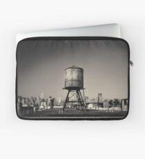 Funda para portátil Imagen sepia de una torre de agua oxidada en un tejado de Queens, en la ciudad de Nueva York, con el puente de Queensboro y el horizonte de Manhattan en el fondo.