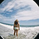 A teenage girl stands at the edge of the sea  by Jean Beaudoin