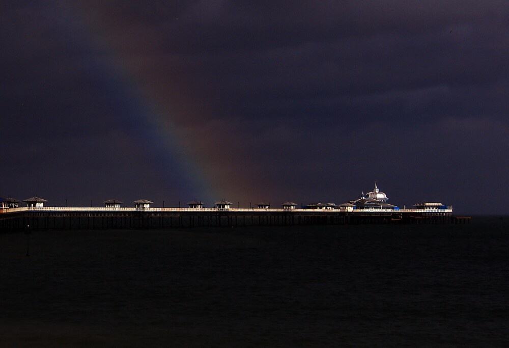 Rainbow at dusk over pier by jimthedrum