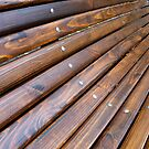 Angled view of a park bench with natural wood texture close up, shallow focus for use as autumn background by vladromensky