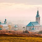 catholic and orthodox churches at foggy sunrise by mike-pellinni