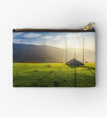 empty hay barrack on a grassy hill at sunrise Studio Pouch