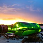 one green bottle laying on the beach by liamcarroll