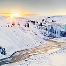 Sunrise over frozen waterfall in Iceland.  by Victoria Ashman