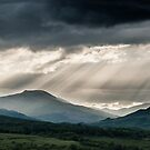 Stormy Scottish Mountains With Rays Of Sunlight by Mark Greenwood