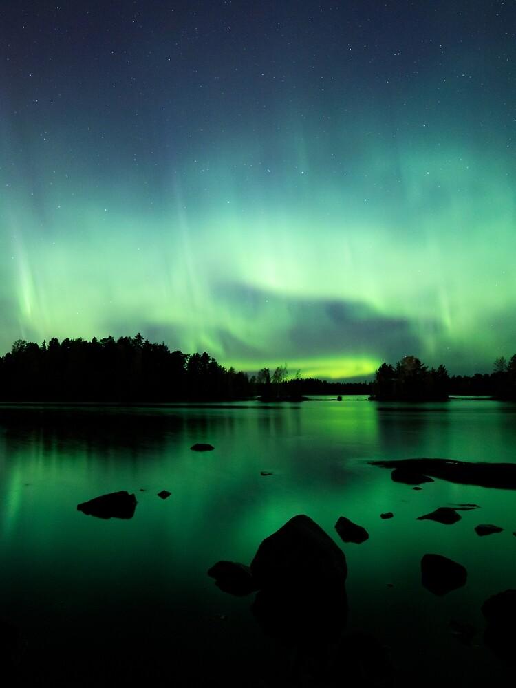 Beautiful northern lights over lake by Juhku