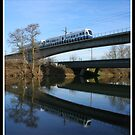 Train crossing over the river by Brett Wall
