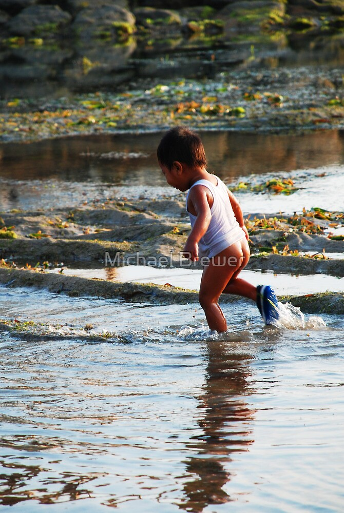 Blissful boy on a Bali beach by Michael Brewer