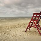 Red Chair on a Cloudy Beach by Kent Nickell