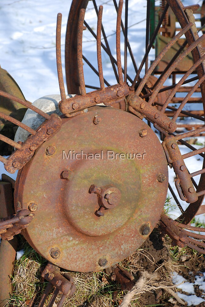 Rusty, abandoned farm equipment in the snow by Michael Brewer