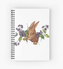 Ostern-Kaninchen, das vom Hintergrund mit Fliedern platzt Spiralblock