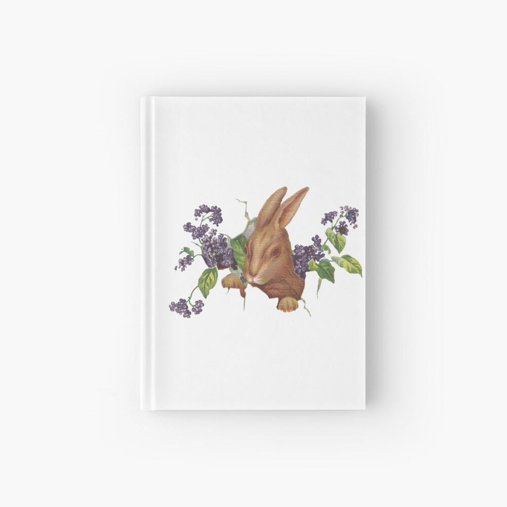 Ostern-Kaninchen, das vom Hintergrund mit Fliedern platzt Notizbuch