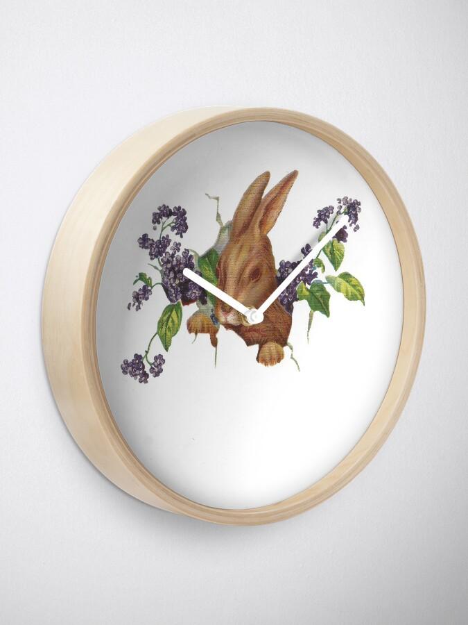 Alternative Ansicht von Ostern-Kaninchen, das vom Hintergrund mit Fliedern platzt Uhr
