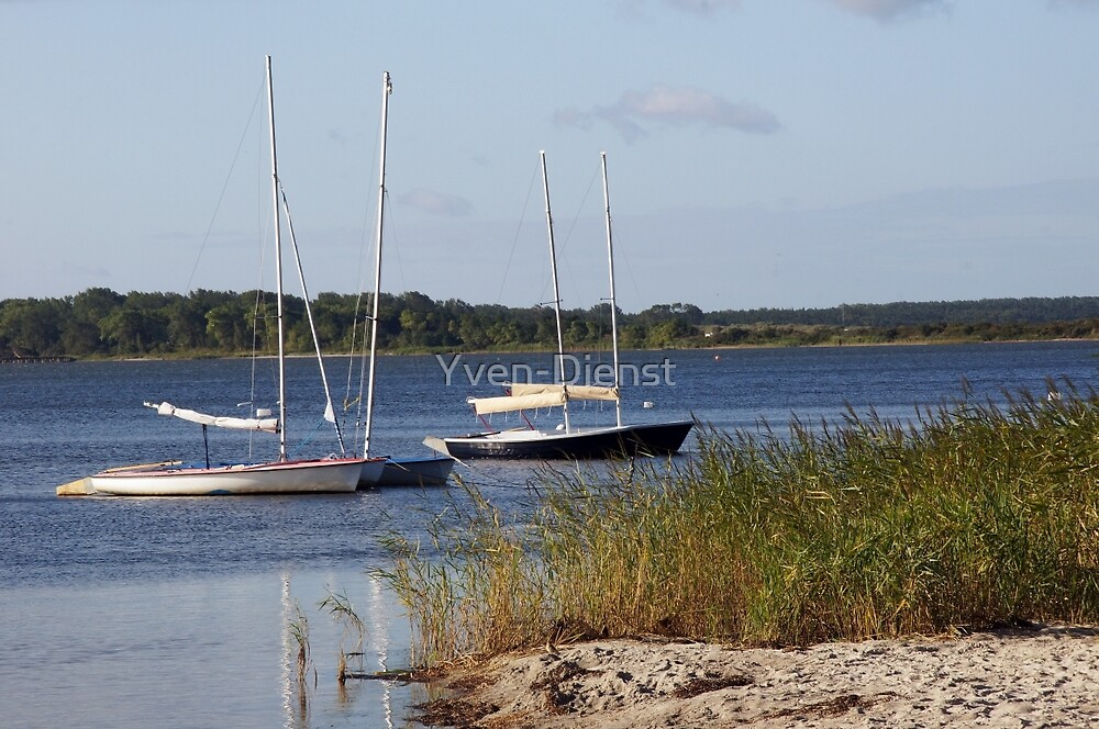 Sailboats moored in front of a natural beach.  by Yven-Dienst