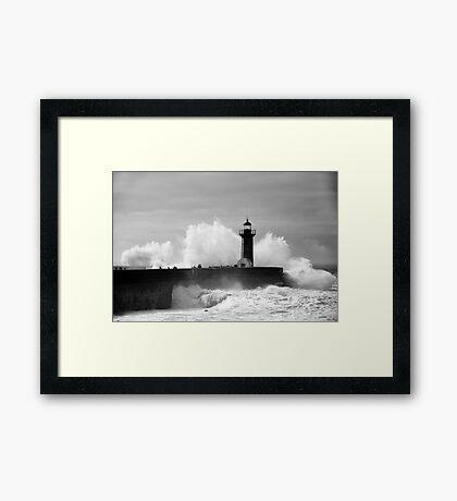 Lighthouse in stormy ocean Framed Print