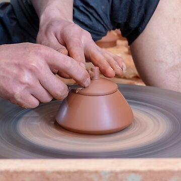 potter in his workshop throws a pot on the potter's wheel by PhotoStock-Isra
