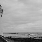 Lighthouse and surfer by Christine Oakley