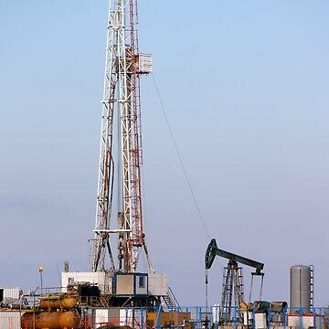 Oil and gas drilling rig and pump jack in oilfield  by goceris