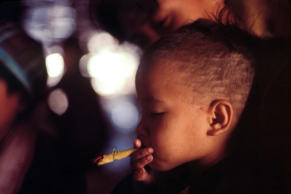 Tribal girl smoking  by John Spies