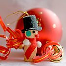 Miniature snowman, red Christmas ball and jingle bell with curled red and gold ribbon by pogomcl