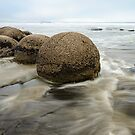 Impressive Moeraki boulders in the blurred Pacific Ocean waves by Sergey Orlov