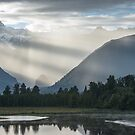 Bright contrast rays of morning sun over the Lake Matheson by Sergey Orlov