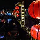 Red paper lanterns on a bridge by Angela Ferguson