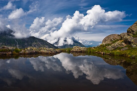 Trolls' clouds reflecting in Norwegian mountain lake. by evimagery