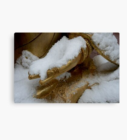 Golden hand in snow. Canvas Print