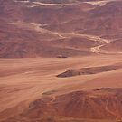 Sand flows through red rock by Owed To Nature