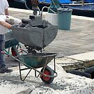 Concrete Pour into Wheelbarrow with Workmen by JHMimaging
