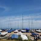 Boats with blue covers under blue sky at Walmer Beach in Kent England by SJMcDermott