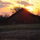 Sunset behind an old red barn by mltrue