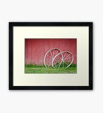 Red barn background with wagon wheels Framed Print